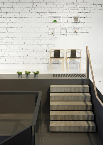 A steel and concrete staircase runs like a ribbon through the Corporate Culture Melbourne showroom, housed inside a former flag factory. Photo by Dianna Snape