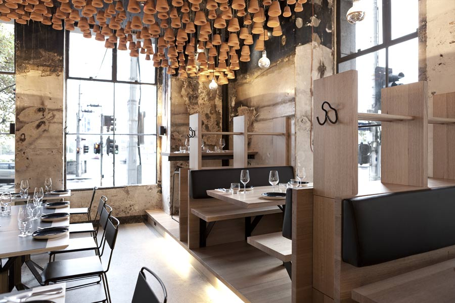 Tasmanian oak booths designed by March Studio line the wall along Exhibition Street, while dining chairs by Daniel Barbera are in keeping with the simple, utilitarian aesthetic