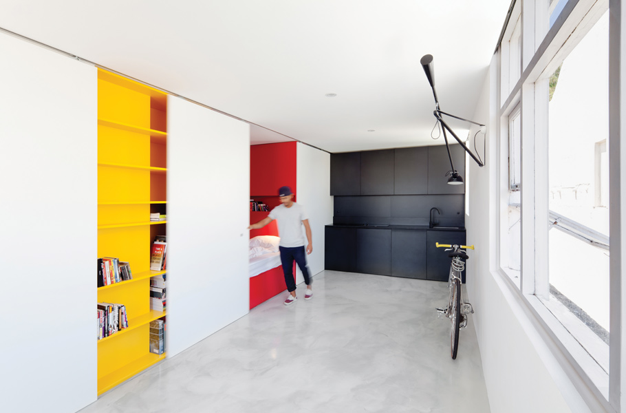 The workings of the apartment are contained within a joinery unit and concealed by sliding doors