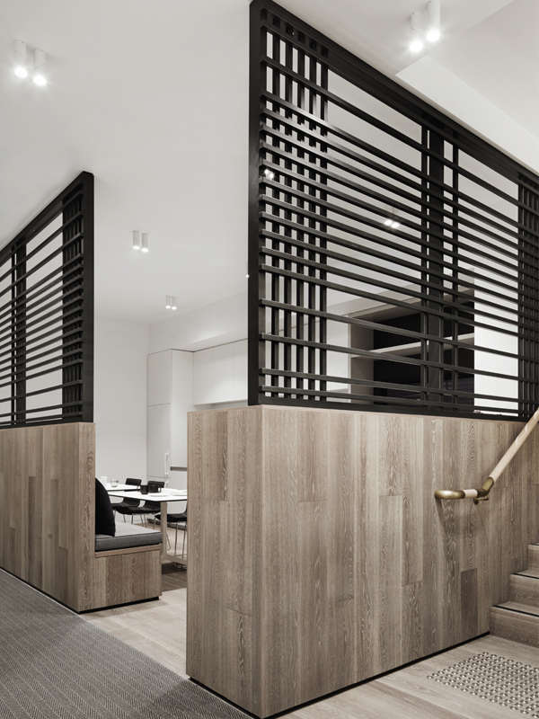 The kitchen and breakout area is separated from the general office area by timber clad walls that feature a black steel custom made lattice screen or 'modern day shutters'