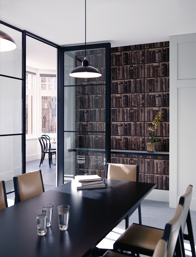 The clubhouse trope of leather bound books is realised in wallpaper