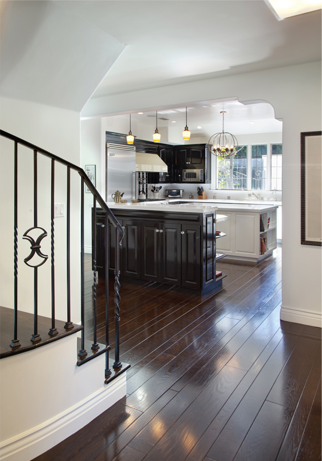 Polished floors throughout typifythe Spanish Revival aesthetic, while a single beam with corbels frames the kitchen space