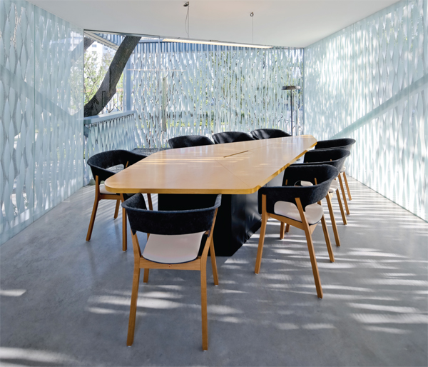 Informal meeting rooms are punctured by existing trees and foliage.