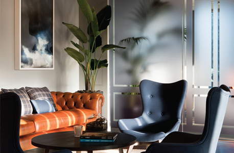 the client waiting area has a 'club-like' atmosphere with a nine- metre, custom-made, banquette sofa with diamond buttoned back in tan leather and groupings of Lloyd high back chairs.