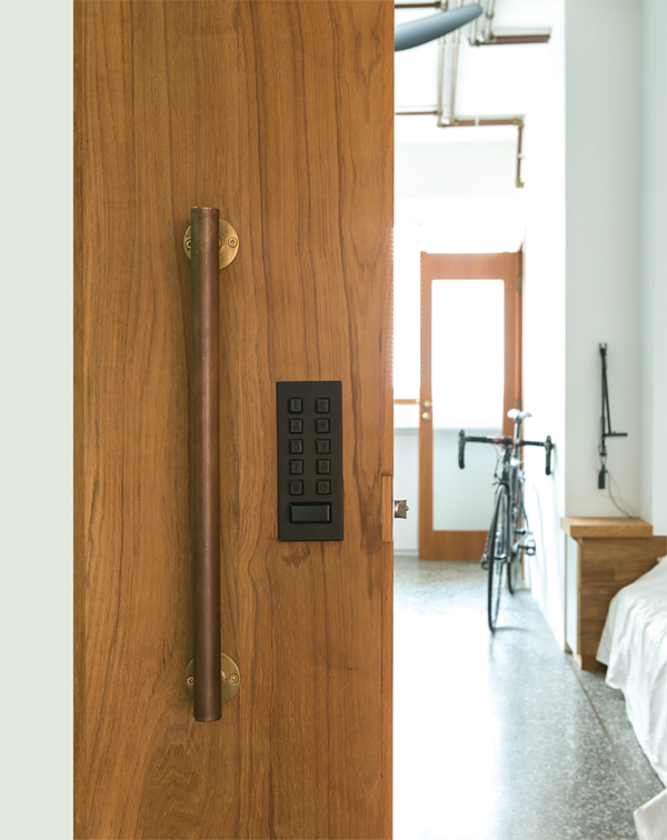 Looking back into the bedroom area from the entrance that features a teak front door with bespoke brass handle.