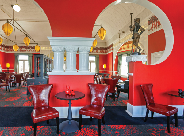 Rich red walls highlight the graceful curves, while red mock-crock seating add a charming element to the Salon de Thé.