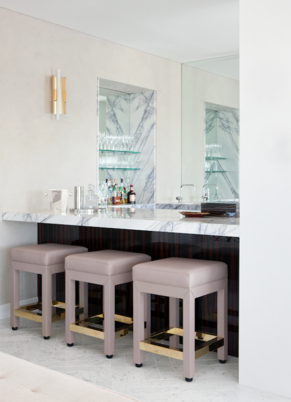 Looking into the bar with marble countertop and Gio Ponti vintage wall sconce.